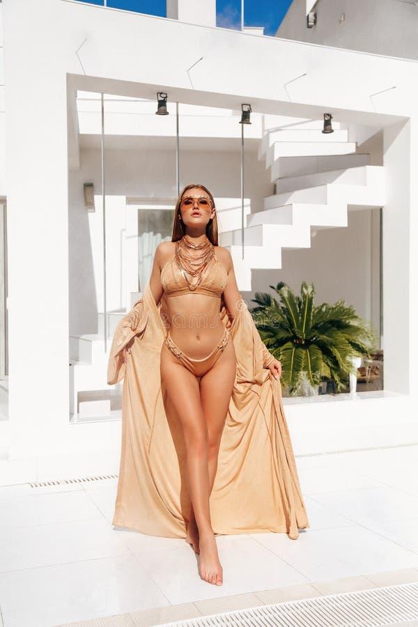 Femme sensuelle avec les cheveux blonds dans le costume de natation élégant posant près de la piscine photo libre de droits