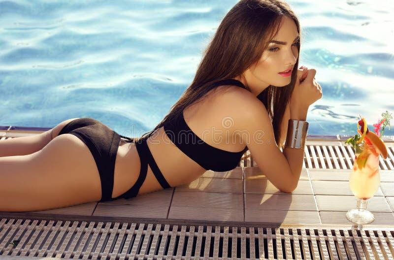 Femme sensuelle avec les cheveux foncés utilisant le bikini élégant, images stock