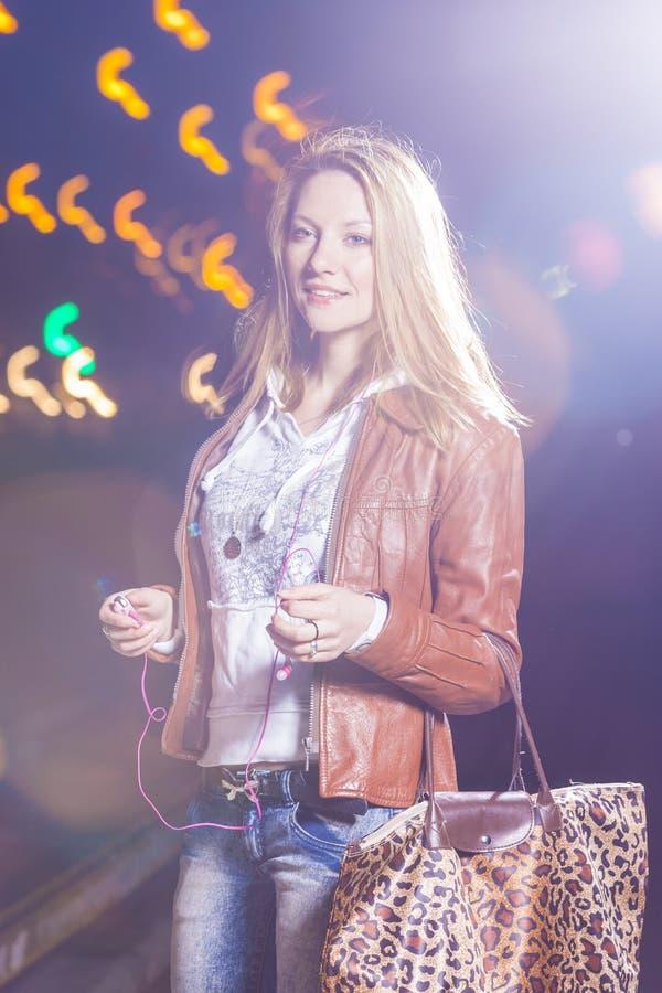 Femme sensuelle et assez caucasienne dans la veste en cuir et des blues-jean posant avec le sac dehors sur la rue image stock