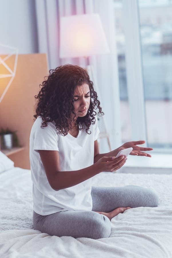 Femme sentant le message inattendu de lecture curieuse de l'ami photos libres de droits