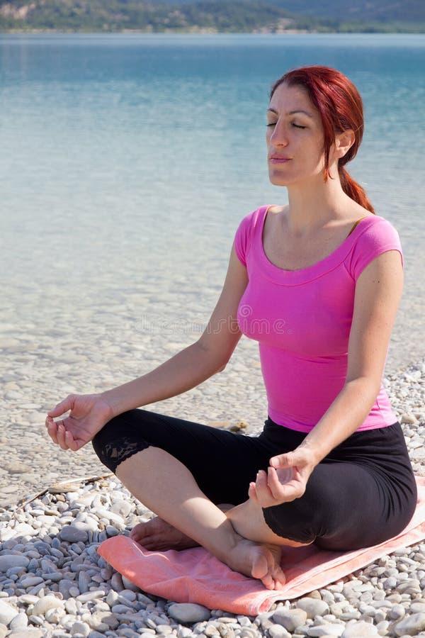 Femme sereine méditant à côté d'un lac. images stock