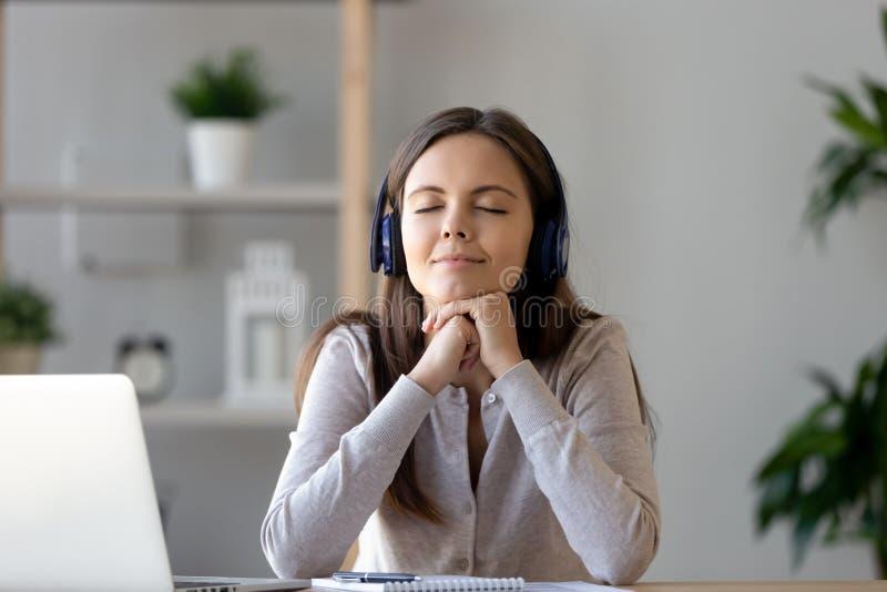 Femme sereine s'asseyant aux écouteurs de écoute d'utilisation de musique de bureau image stock