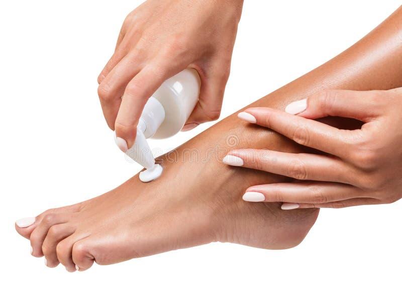Femme serrant hydratant la crème sur sa jambe photos stock