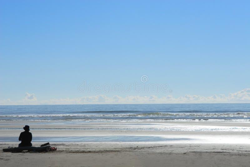 Femme seul s'asseyant à la plage photo stock
