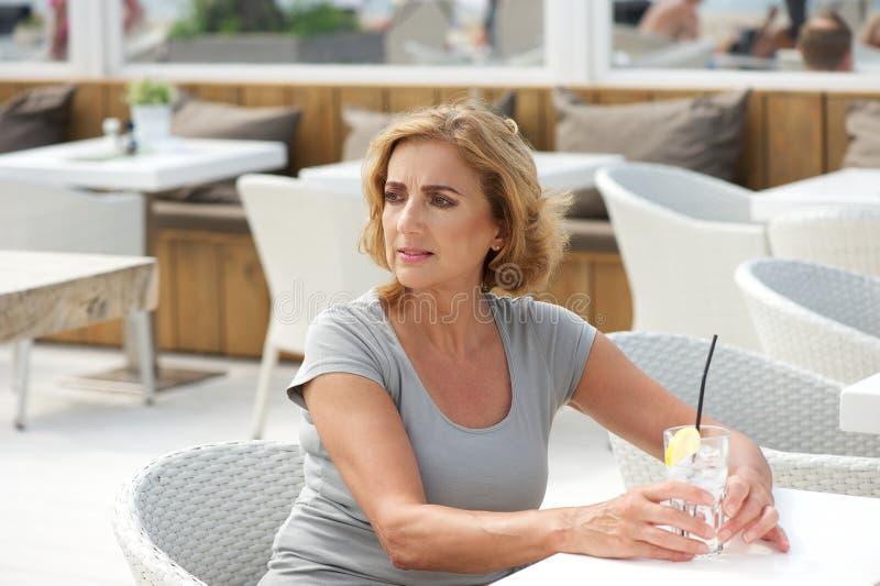 Femme seul s'asseyant avec un verre de l'eau au restaurant images stock