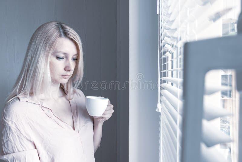 Femme seule apathique triste avec une tasse de café regardant par une fenêtre à la maison ou le concept d'hôtel, de divorce, de d photos stock