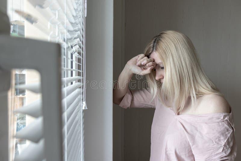 Femme seule apathique triste regardant par une fen?tre ? la maison ou le concept d'h?tel, de divorce, de d?pression et d'apathie photos stock