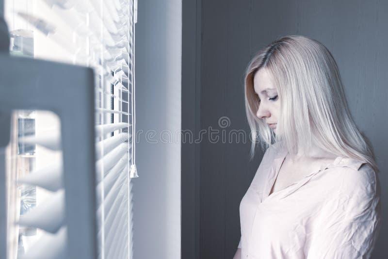 Femme seule apathique triste regardant par une fen?tre ? la maison ou le concept d'h?tel, de divorce, de d?pression et d'apathie photo libre de droits
