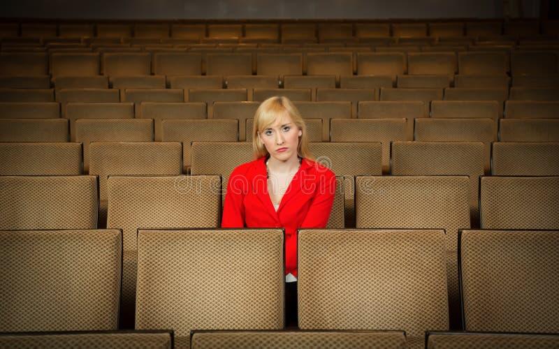 Femme seule et déprimée seul s'asseyant dans le théâtre vide photographie stock