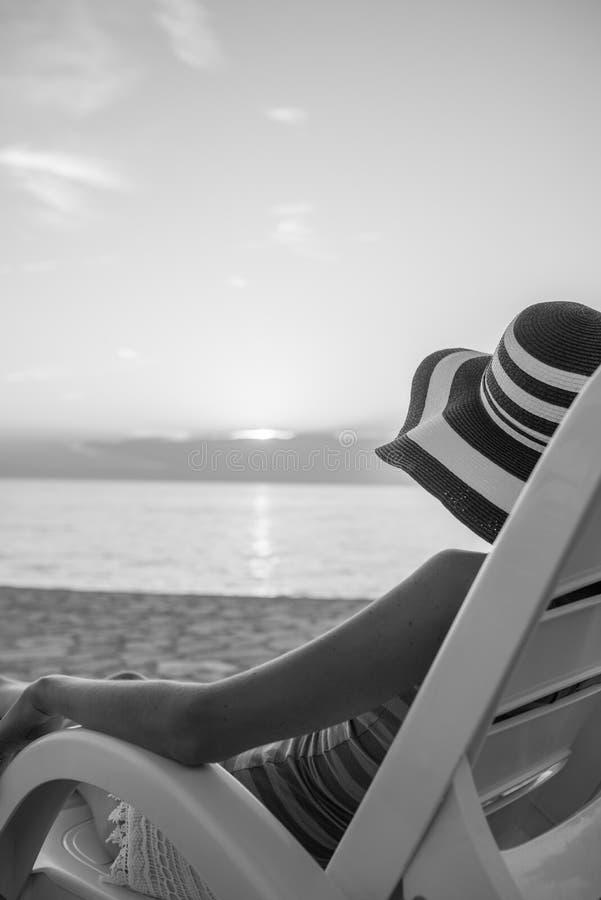 Femme seule regardant le coucher du soleil comme elle détend sur un recliner Chai images libres de droits