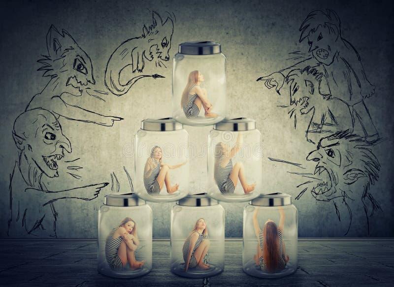 Femme seule s'asseyant dans une pile des pots en verre entourés par les hommes mauvais négatifs fâchés photos stock