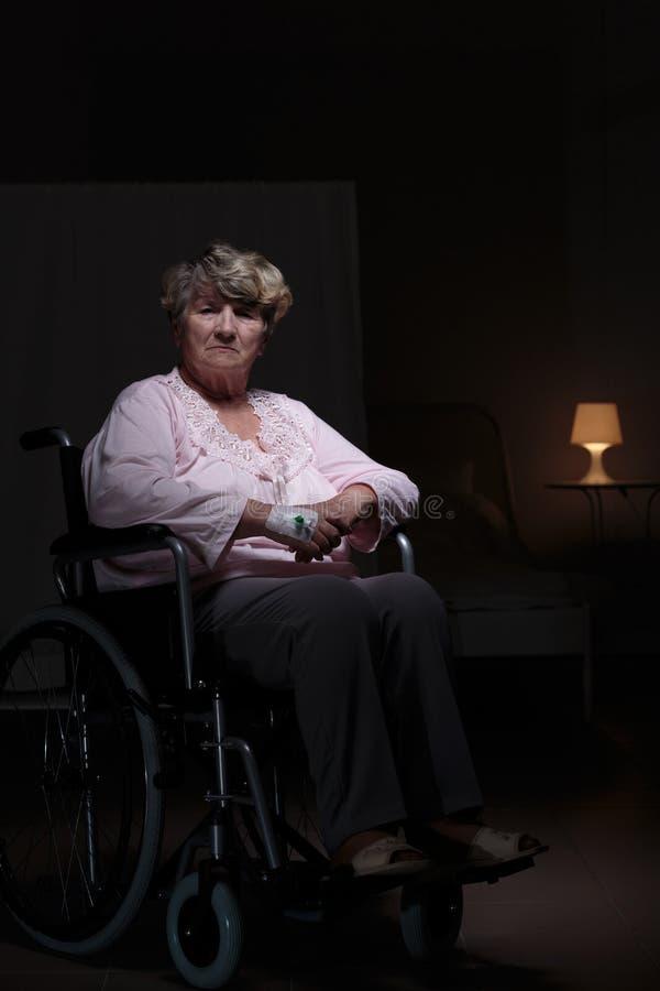 Femme seule s'asseyant sur le fauteuil roulant photos libres de droits