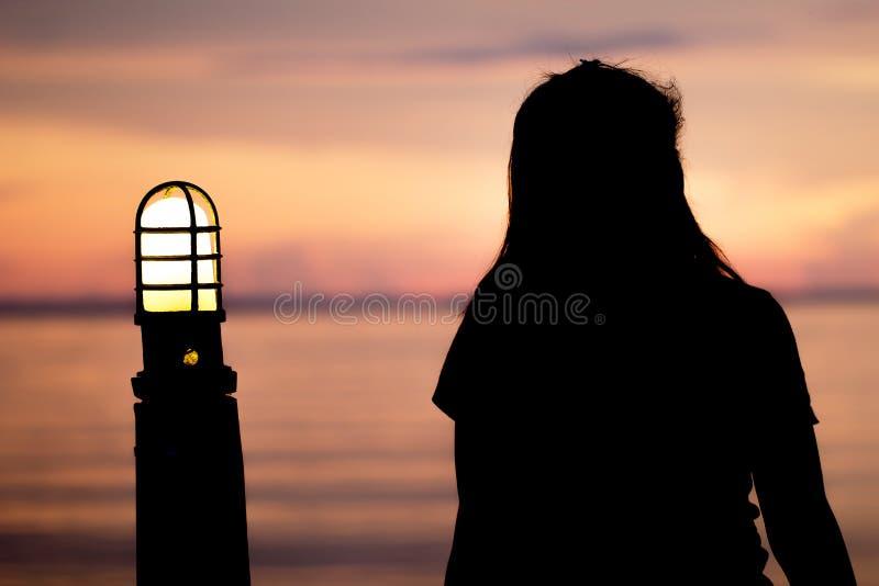 Femme seule seul s'asseyant à un moment où coucher du soleil de mer sont le beau style abstrait images stock