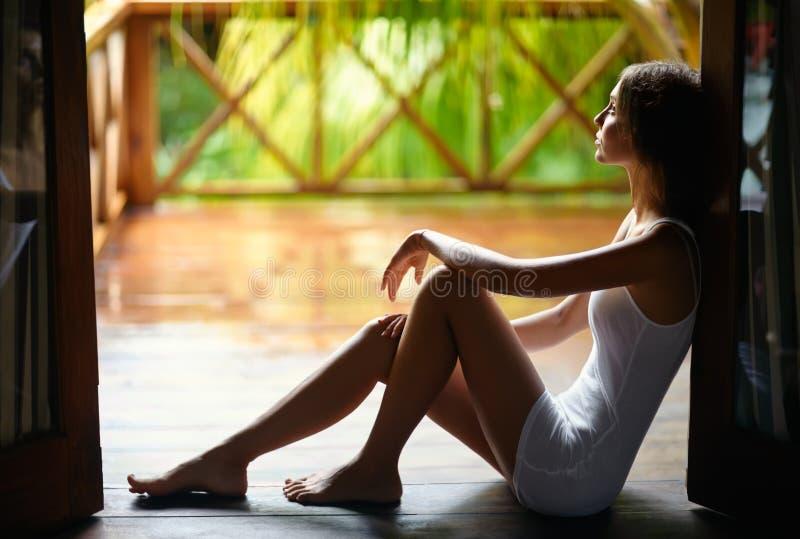 Femme seule triste s'asseyant sur le porche pendant la pluie image libre de droits