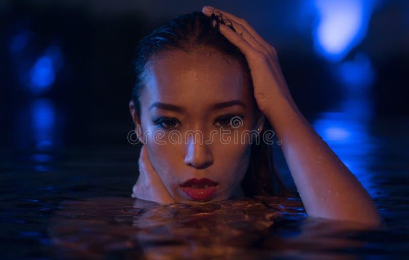 Femme sexy à la piscine dans le temps de soirée photos libres de droits