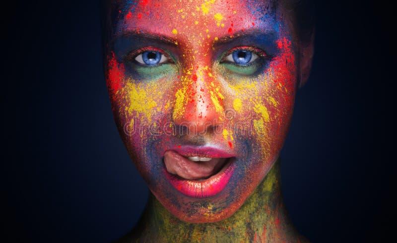Femme sexy avec le maquillage créatif lumineux léchant ses lèvres image libre de droits