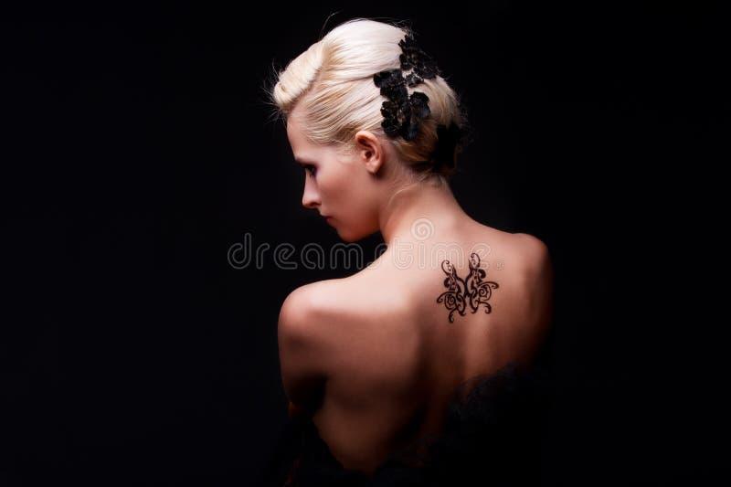 Femme sexy avec le tatouage sur elle en arrière photos libres de droits