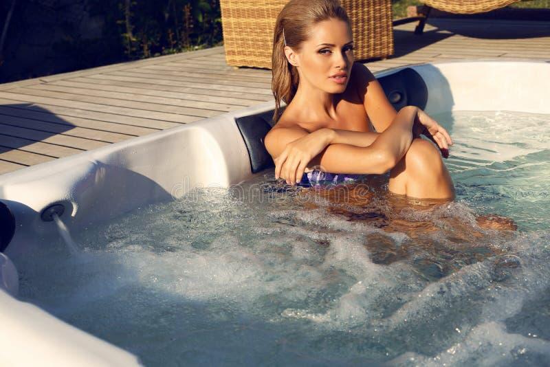Femme sexy avec les cheveux blonds détendant dans le tourbillon extérieur images stock