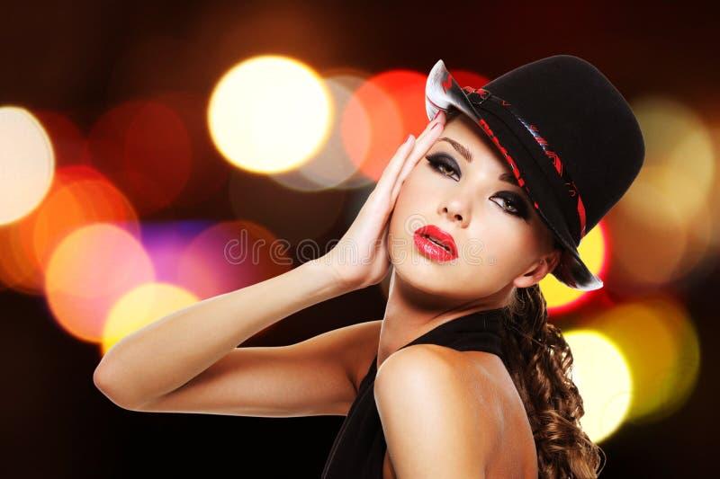 Femme sexy avec les lèvres rouges lumineuses et le chapeau à la mode images stock