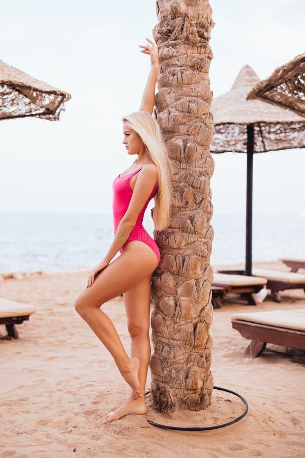 Femme sexy blonde de beauté dans le maillot de bain rose près du palmier sur la plage de station de vacances à la vocation d'été photo stock