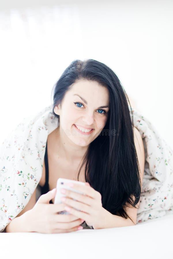 Femme sexy d'une chevelure noire détendant et à l'aide du téléphone portable sur le lit photo stock