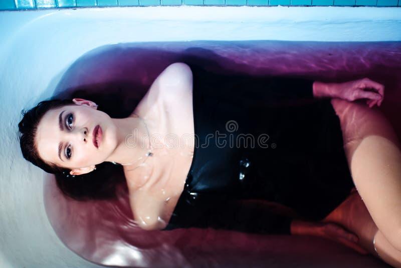 Femme sexy dans la combinaison dans le bain Lumière lumineuse et eau colorée Épaules nues image stock