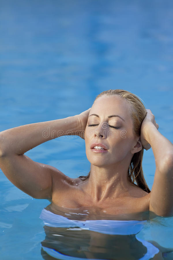 Femme sexy dans le bikini blanc dans la piscine images libres de droits