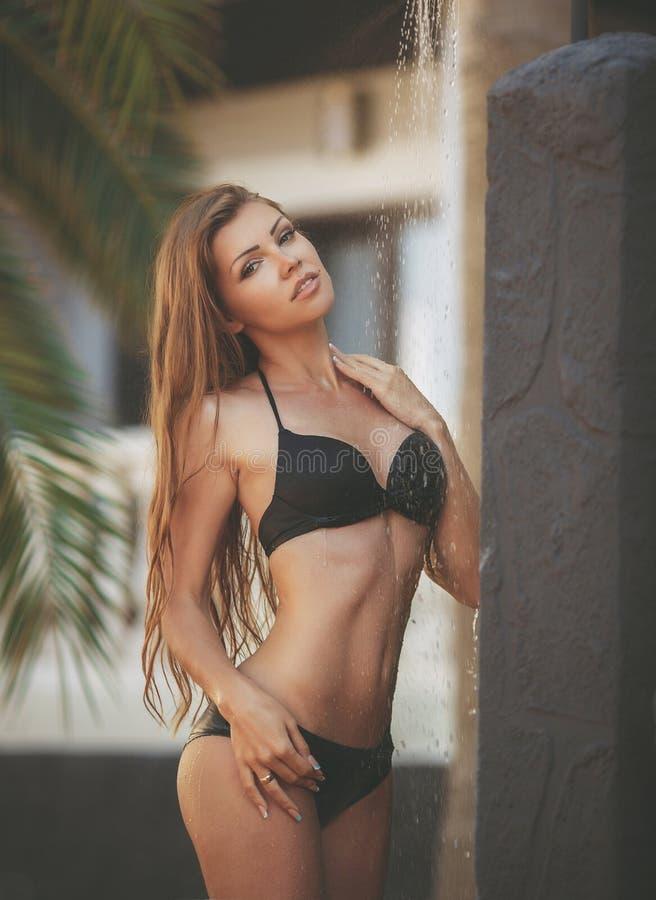 Femme sexy dans les palmiers autour et la douche de pluie images libres de droits