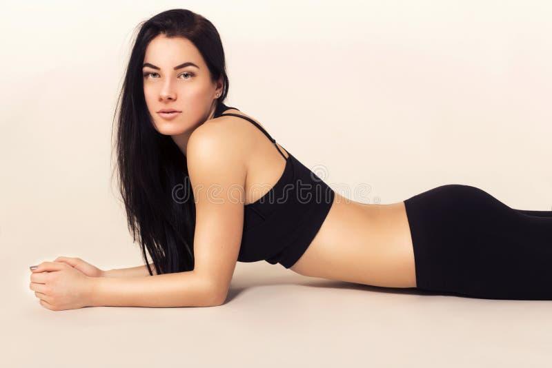 Femme sexy de brune d'ajustement dans les vêtements de sport se trouvant sur le plancher photo stock