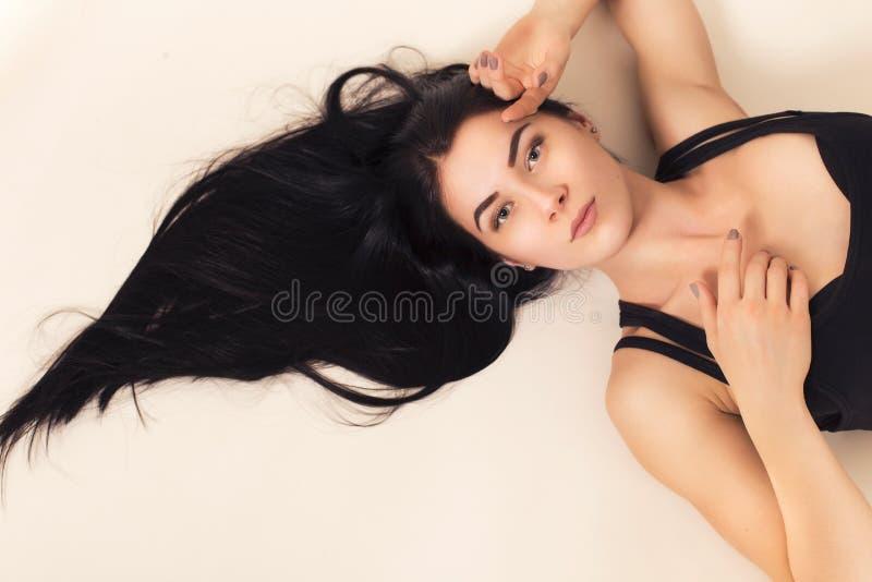Femme sexy de brune d'ajustement dans les vêtements de sport se trouvant sur le plancher, cheveux f photographie stock libre de droits