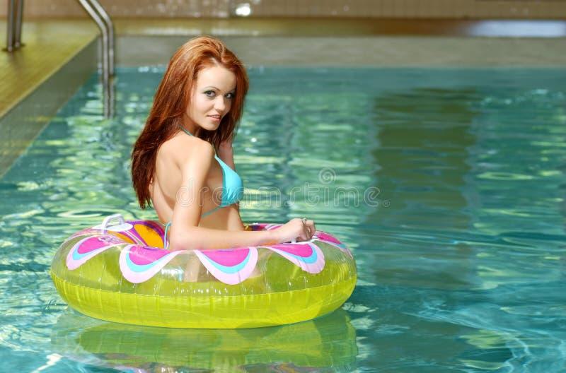 Femme sexy de brunette dans un jouet de flottement de l'eau images libres de droits