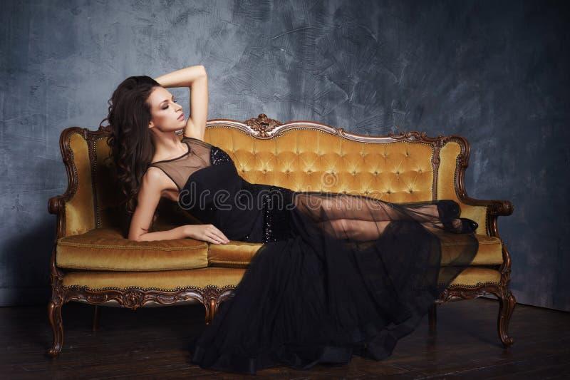 Femme sexy et belle dans la robe noire sur un sofa photographie stock