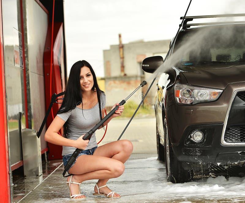 Femme sexy lavant le sourire de voiture photo stock