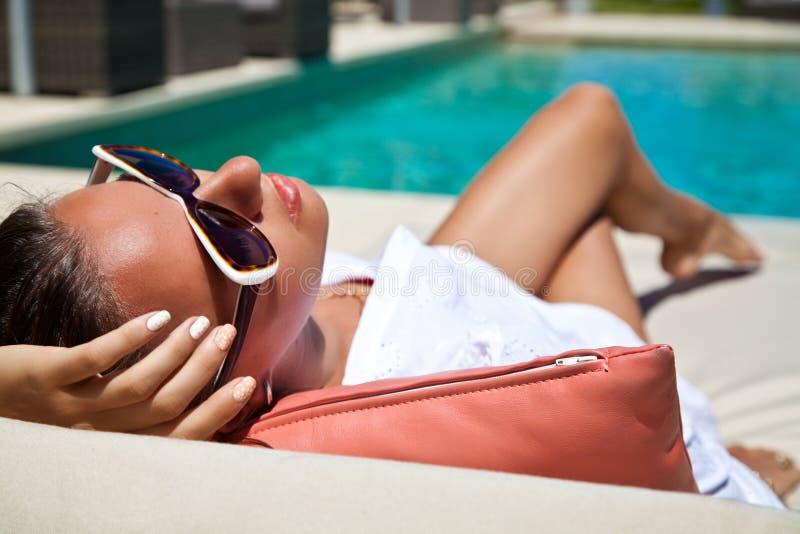 Femme sexy prenant un bain de soleil à la station de vacances de piscine photo libre de droits