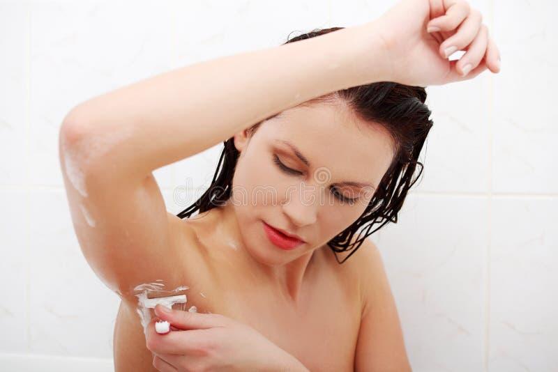 Femme sexy rasant son aisselle pendant le bain. image libre de droits
