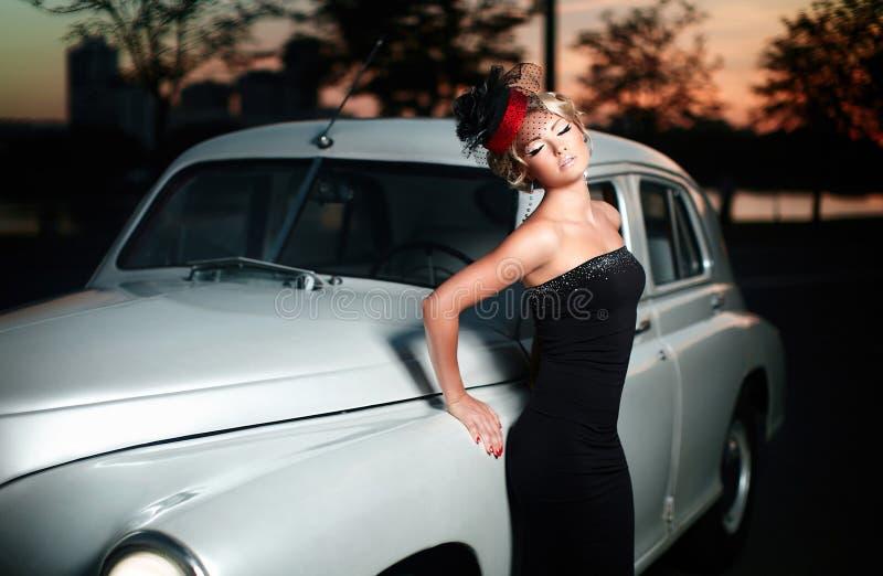 Femme sexy restant le véhicule proche dans le rétro type photo libre de droits