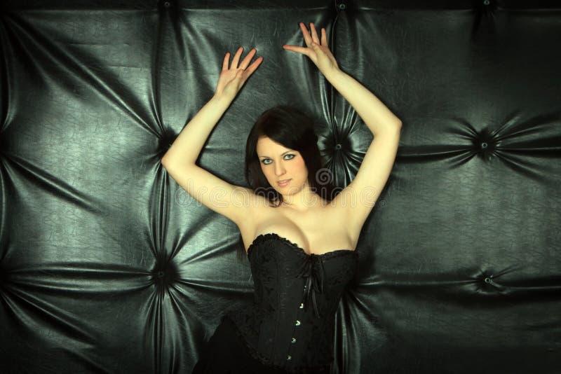 Femme sexy se trouvant sur le sofa en cuir noir image stock