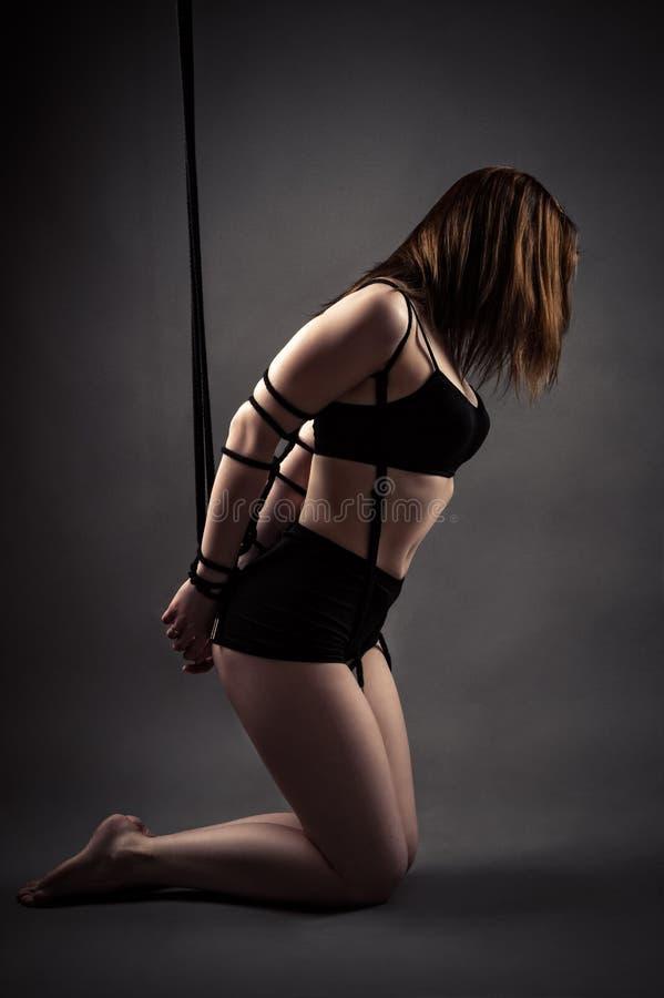 Femme slave sexy se mettant à genoux avec les mains attachées images libres de droits