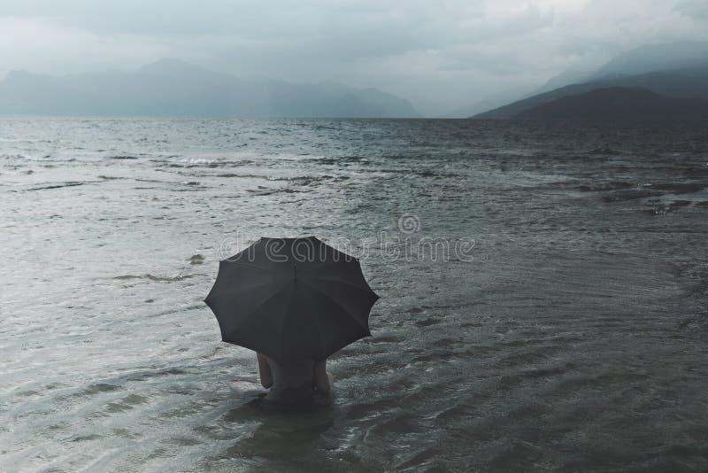 Femme solitaire avec la pluie de attente de parapluie se reposant en mer photo stock
