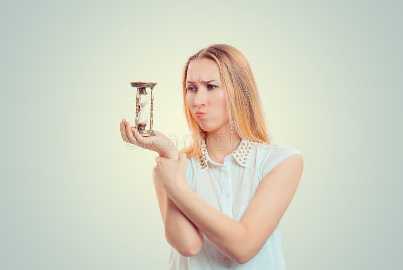 Femme sombre bouleversée regardant le sablier photo stock