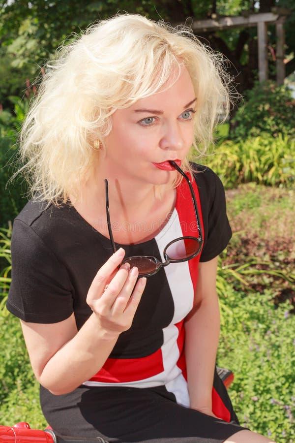 Femme songeuse avec des lunettes de soleil photo stock