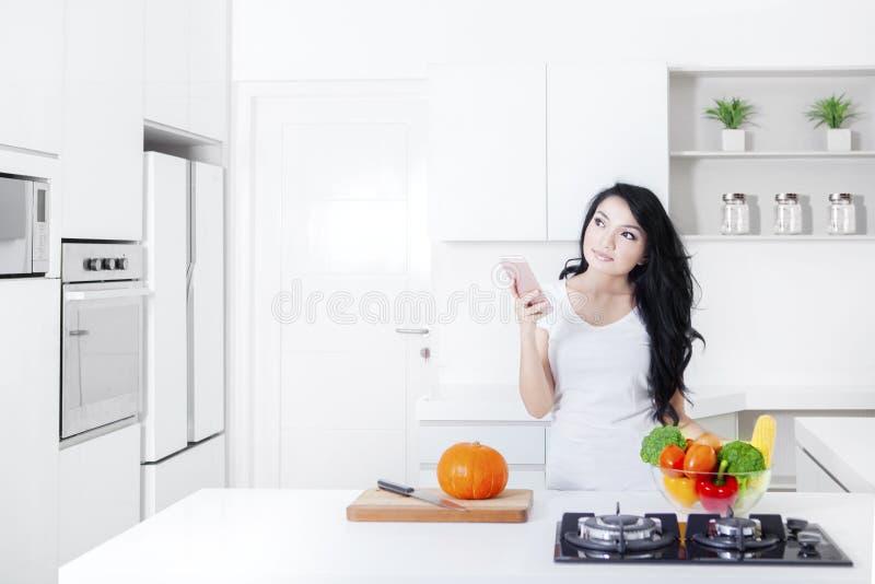 Femme songeuse avec le smartphone dans la cuisine images stock