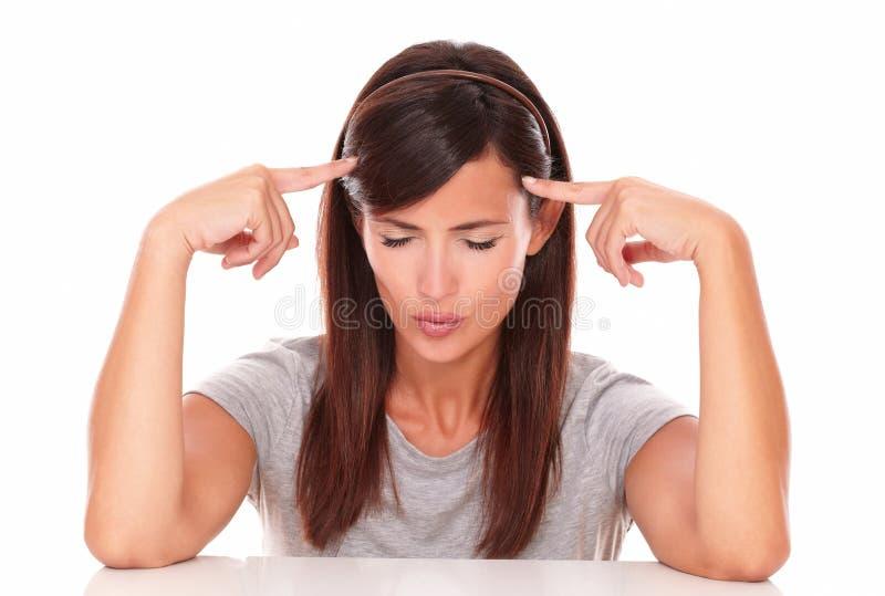 Femme songeuse avec ses doigts sur la tête photo libre de droits