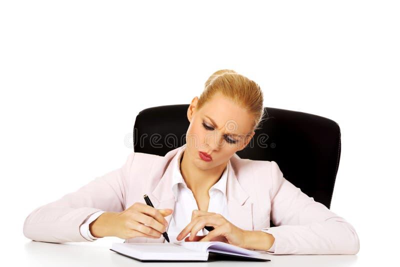 Femme songeuse d'affaires prenant des notes derrière le bureau photos stock