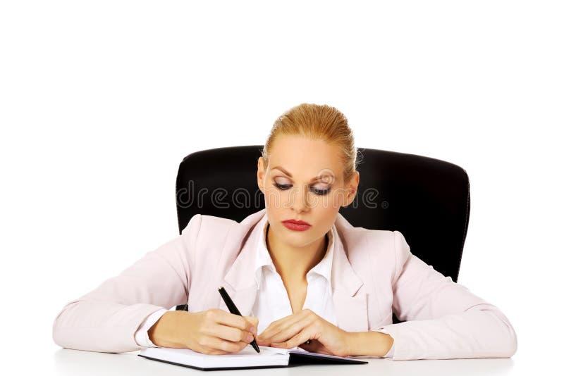 Femme songeuse d'affaires prenant des notes derrière le bureau photographie stock