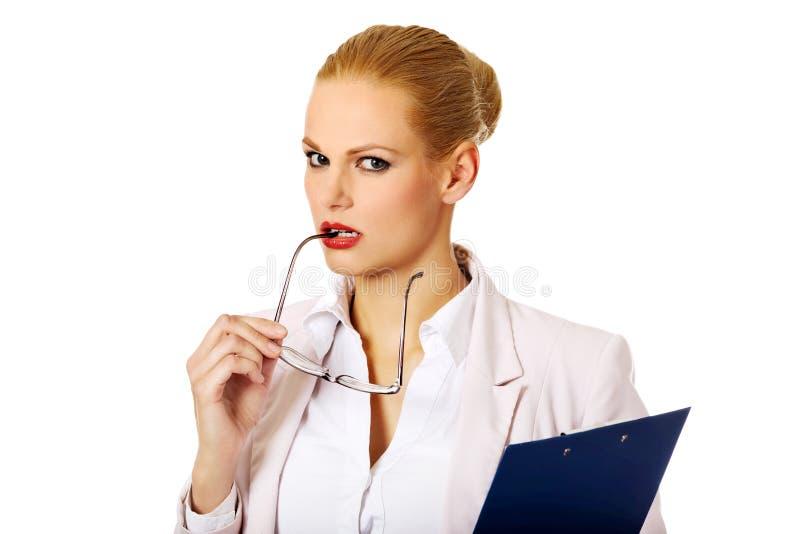 Femme songeuse d'affaires tenant un presse-papiers et des verres photos libres de droits