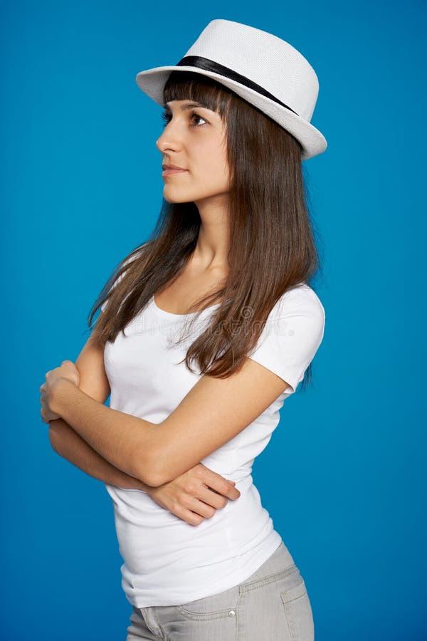Femme songeuse dans un chapeau de paille regardant au côté images libres de droits