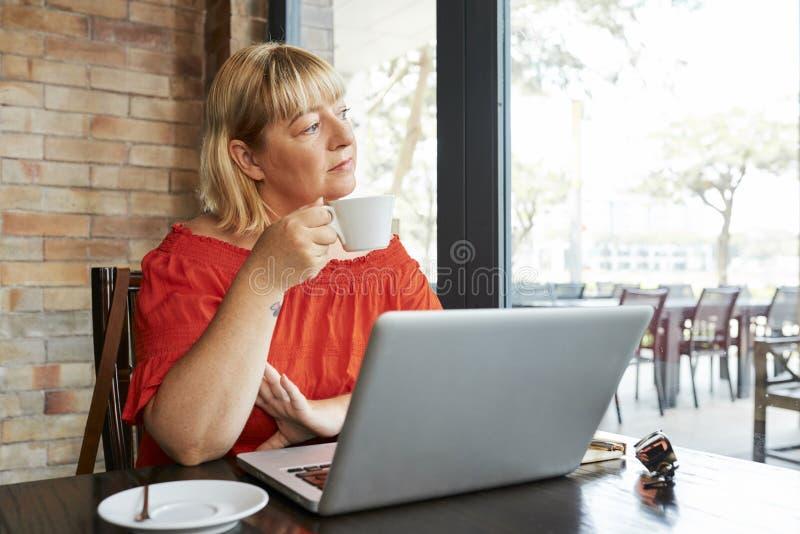Femme songeuse en caf? photographie stock