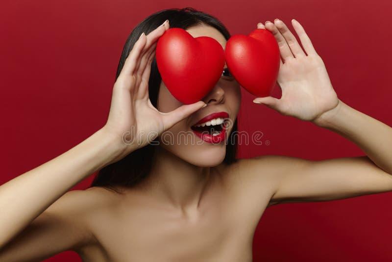 Femme sortie gaie de brune tenant des coeurs Portrait de Saint-Valentin du studio de sourire attrayant de femme tiré avec des coe photos libres de droits