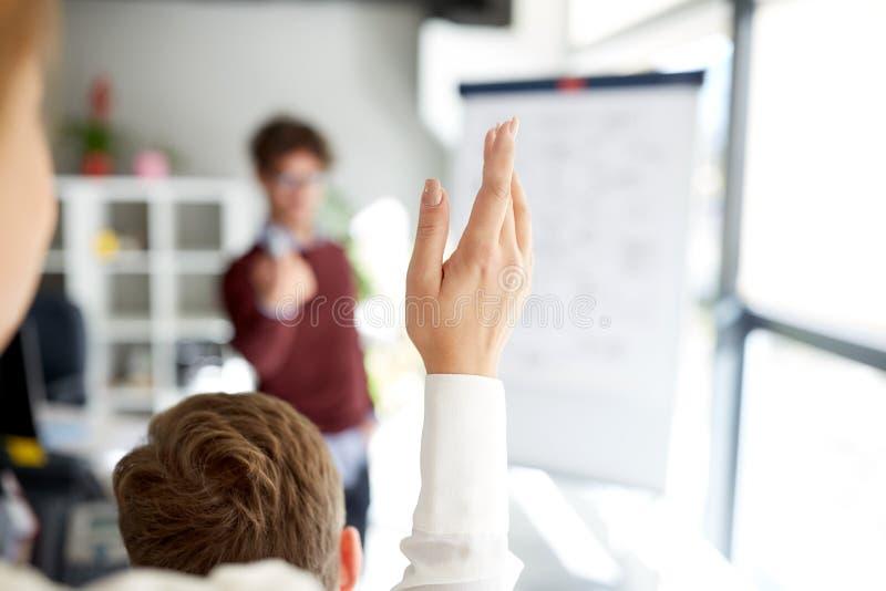 Femme soulevant la main à la présentation dans le bureau photographie stock